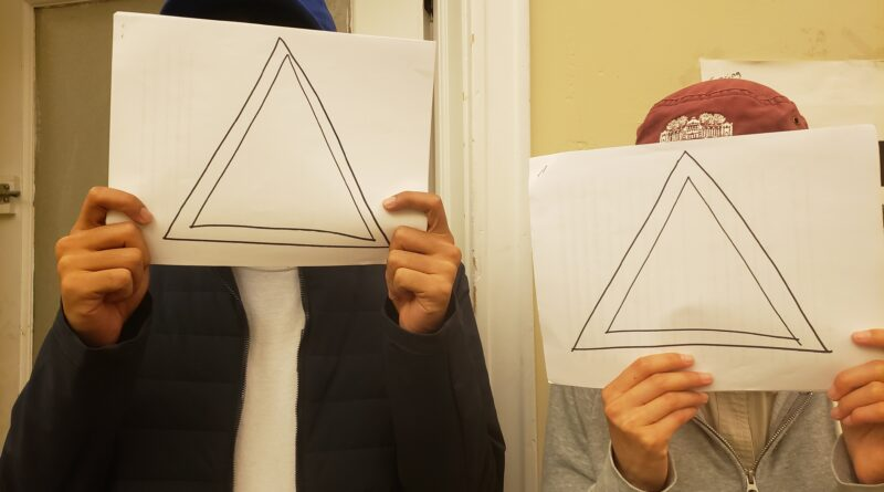"""Two people whose faces are covered with the """"Delta"""" symbol"""